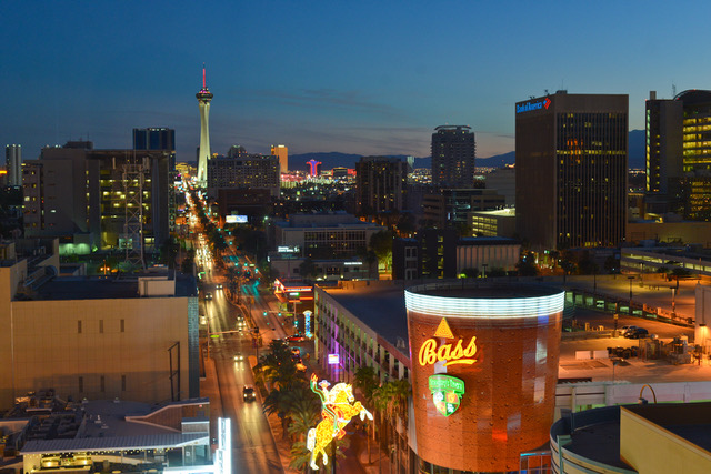 Aerial view of Downtown Las Vegas at night with the Strip in the distance