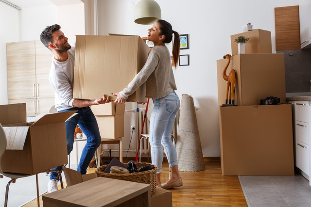 Man and woman moving boxes in their new home