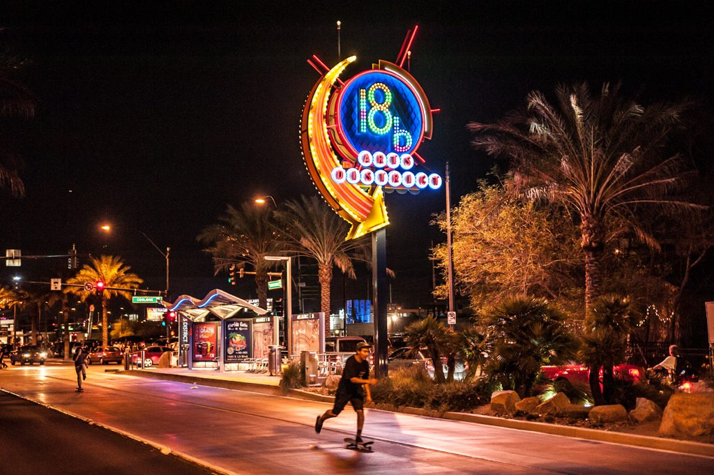 The 18b Arts District sign in Las Vegas at night as a man rides by on a skateboard