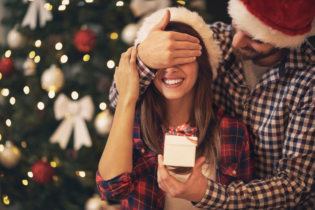 Man holding his hand over the woman's eyes and holding a present in front of her, while wearing Santa Claus hats with a Christmas tree in the background