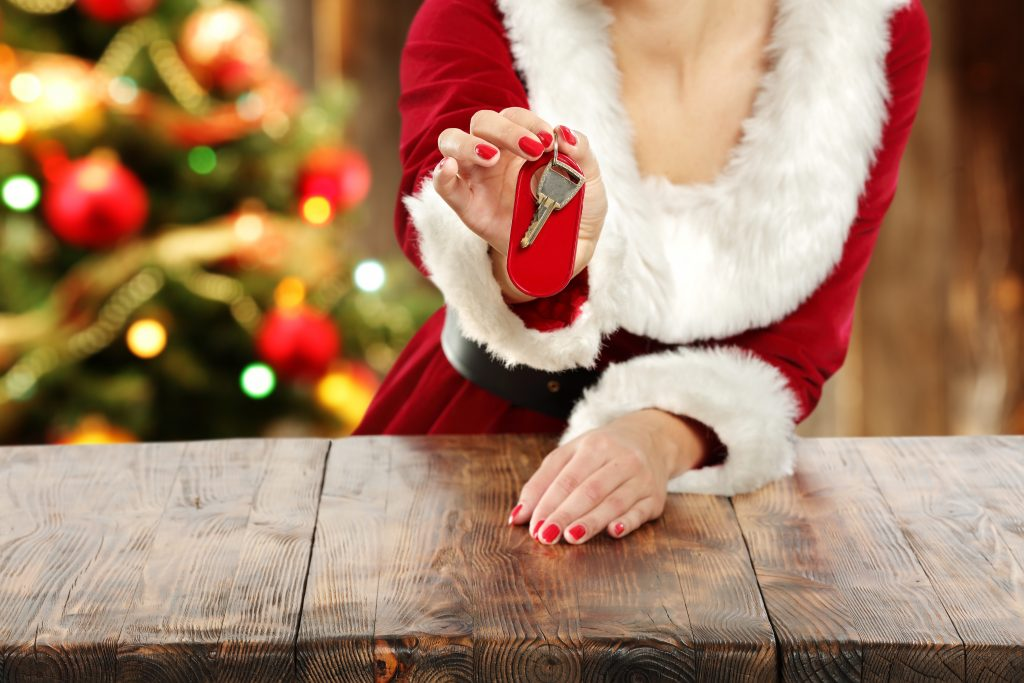 Woman wearing a Santa Claus costume and holding up a pair of keys