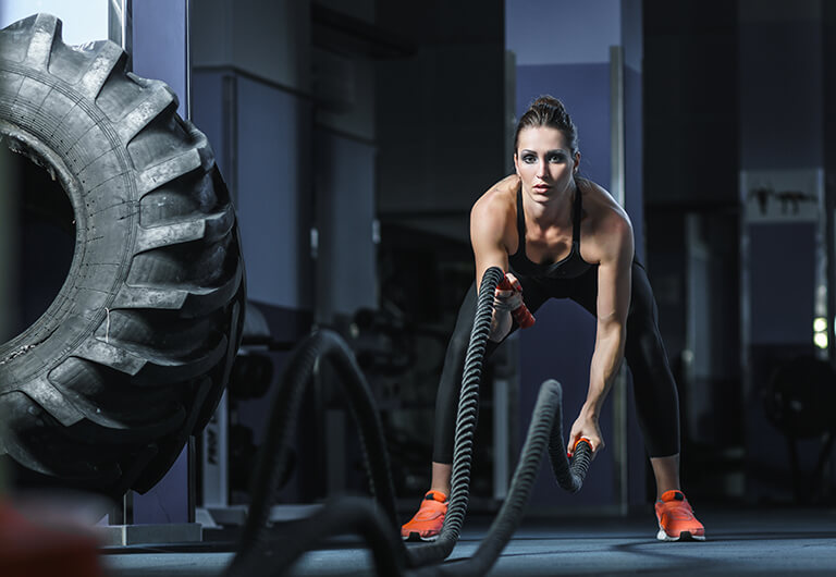 Woman working out during a crossfit class with ropes.