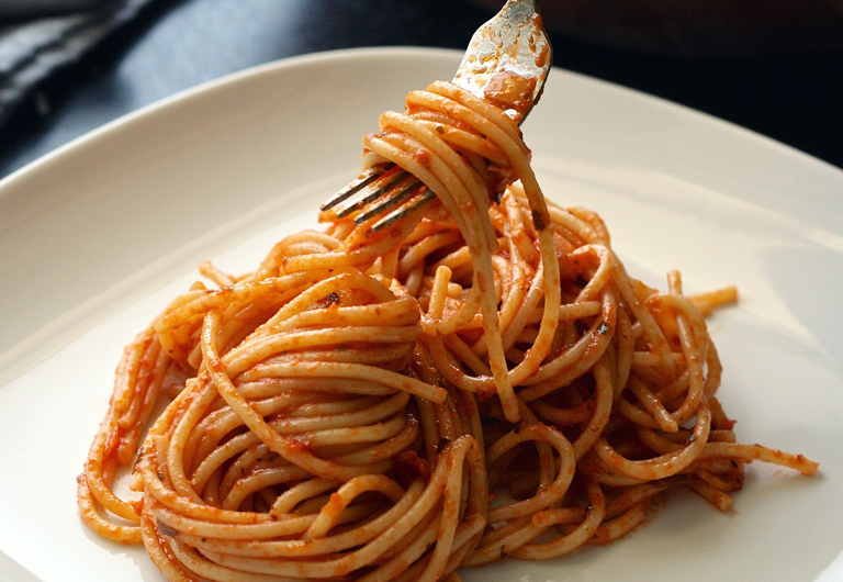 Fresh spaghetti being twirled with a fork.