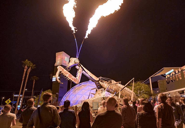 Giant praying mantis sculpture blowing fire in Downtown Container Park.